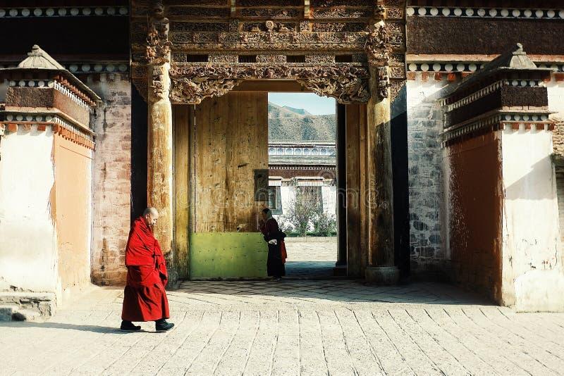 тибетский монах идя в прошлом одним из виска пока женщина паломника моля на заднем плане стоковые изображения