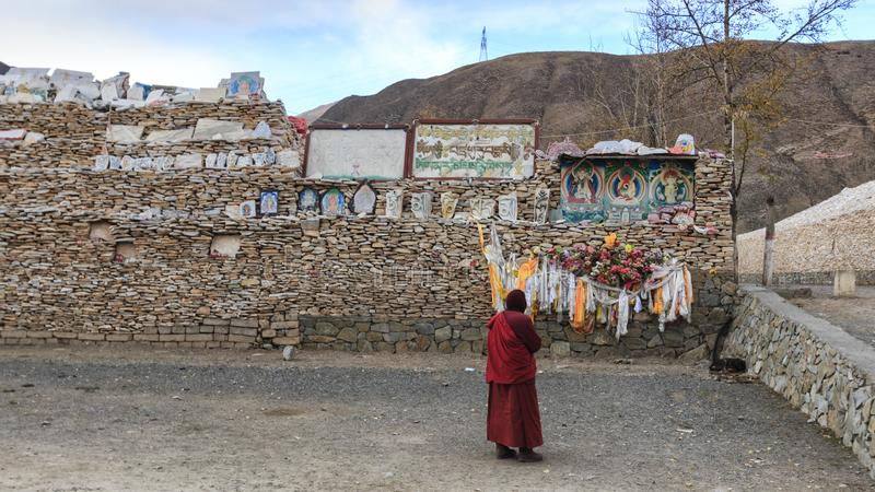 Тибетский монах моля перед камнями Mani на стене Mani Shicheng виска Mani с буддийским engrav жужжания Om Mani Padme мантры стоковое изображение