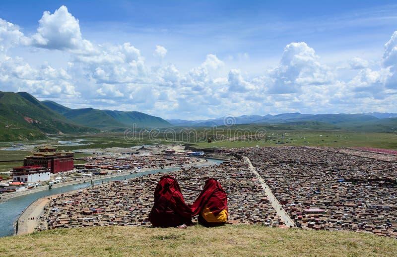 Тибетский монах сидя на холме в Сычуань, Китае стоковое изображение