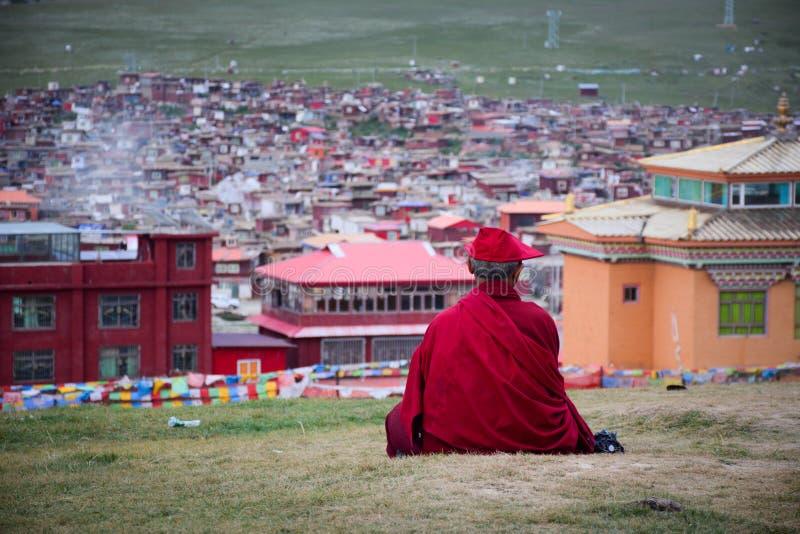 Тибетский монах сидя на холме в Сычуань, Китае стоковая фотография rf