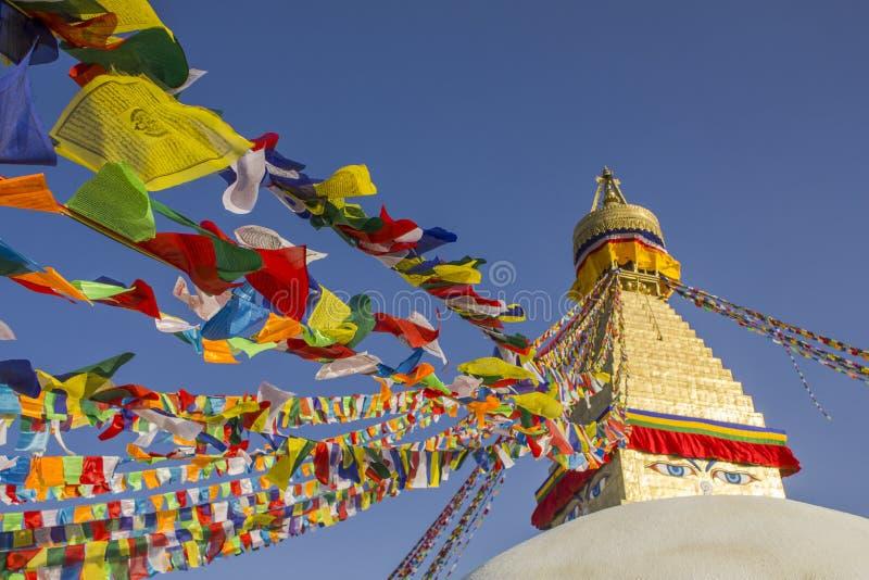 Тибетское буддийское Stupa Bodhnath с глазами и пестроткаными флагами молитве против чистого голубого неба на дневном времени стоковая фотография rf