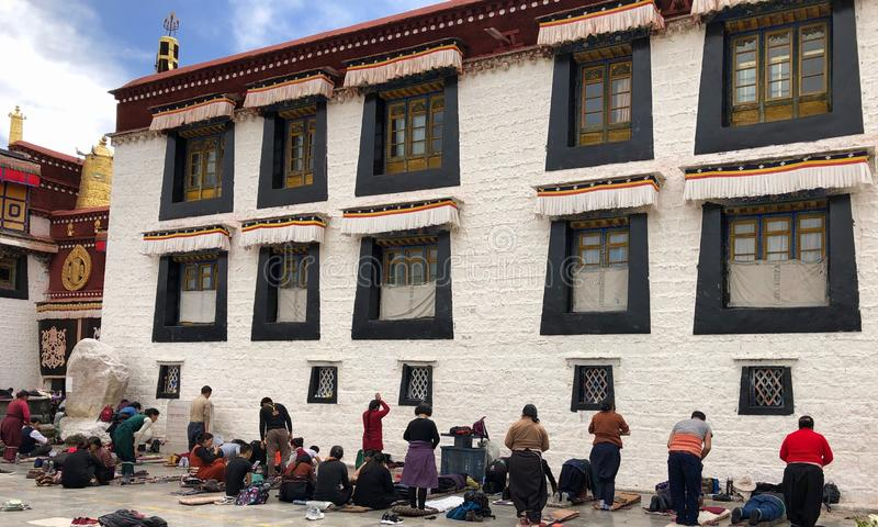 Тибет, Китай - апрель 2019: Паломники моля перед тибетским виском в Лхасе, Тибете стоковое фото