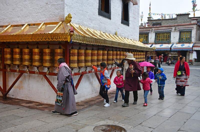 Тибет, Лхаса, Китай, 3-ье июня 2018 Буддисты закручивая ритуальные барабанчики рядом с одним из небольших старых буддийских монас стоковая фотография