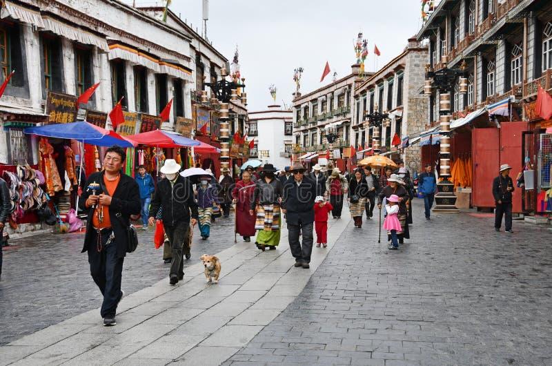 Тибет, Лхаса, Китай, 3-ье июня 2018 Люди идя в старый дождь гостиницы Лхасы городка стоковые фотографии rf