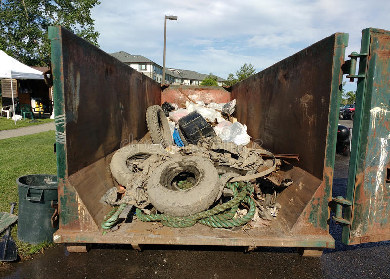 Тинная погань в мусорном контейнере собранном во время события уборки, автошинах предусматриванных в грязи стоковое изображение rf