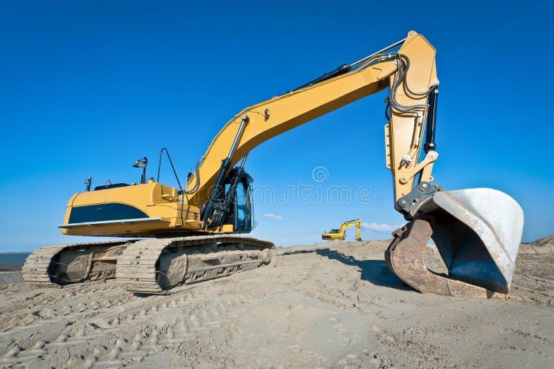 2 типа след машины экскаватора на работе earthmoving стоковые изображения