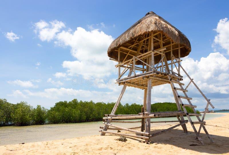 Типичная бамбуковая хижина личной охраны с листьями ладони стоя на пляже песка благоговения нашивки на предпосылке зеленых мангро стоковое изображение