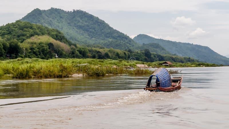 Типичная длинн-замкнутая шлюпка проводит Меконг в Luang Prababang, Лаосе стоковые фотографии rf
