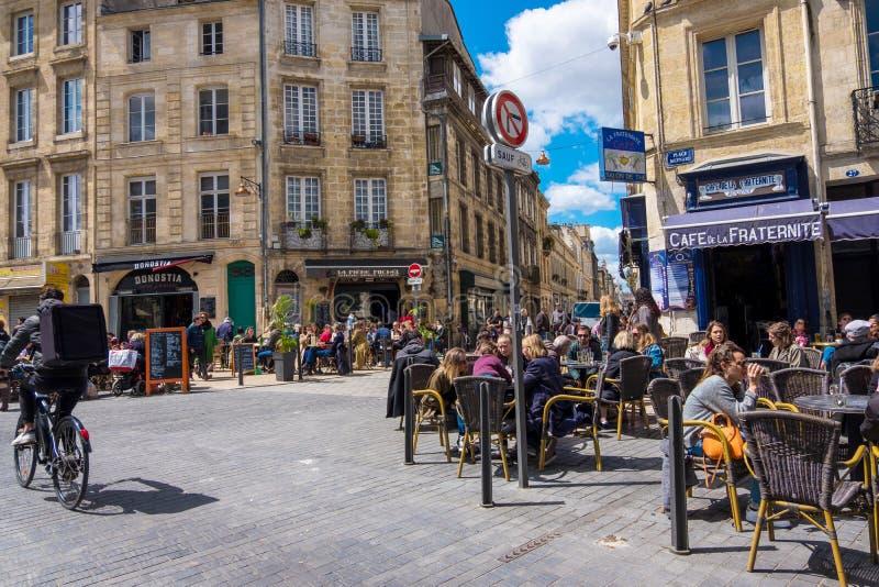 Типичная сцена города Бордо Резиденты города и туристы ослабляют в кафе на улице в Бордо, Франции стоковая фотография