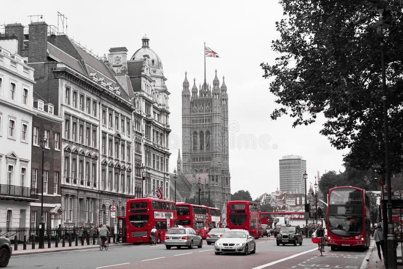Типичная улица Лондона со своими шинами и парламентом красного цвета в b стоковая фотография rf