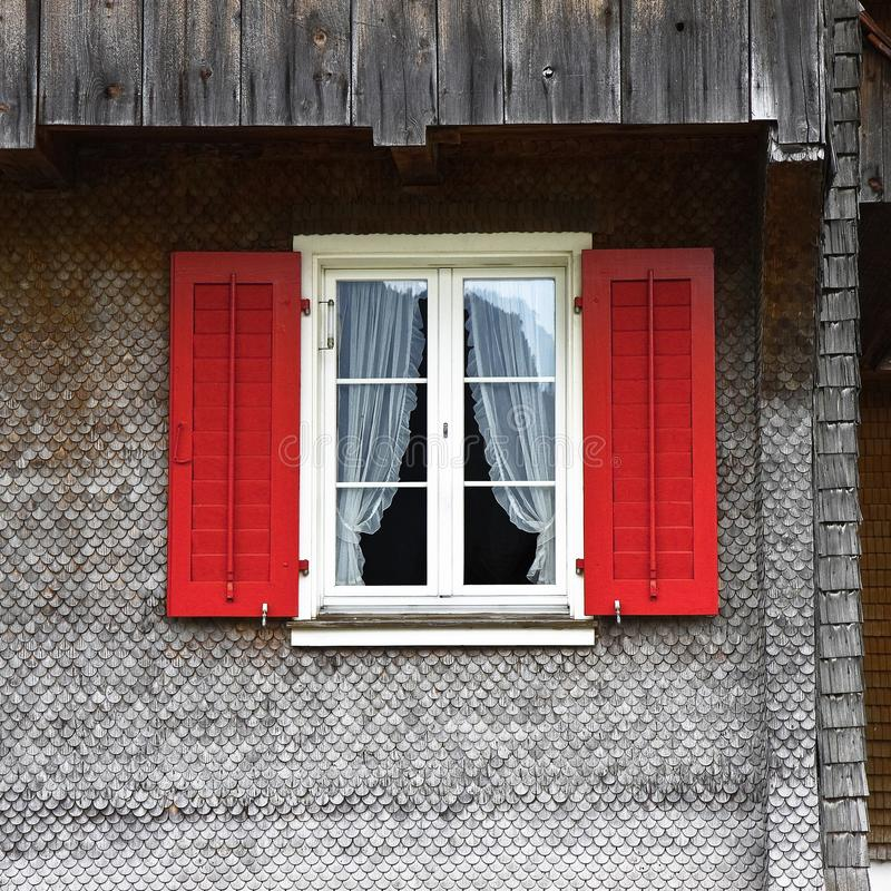 Типичное швейцарское окно с штарками в красном цвете стоковая фотография rf