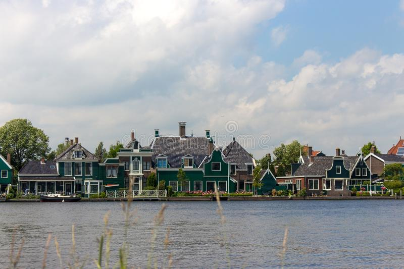 Типичные голландские здания на стороне реки Архитектура Голландии Загородные дома в Zaanse Schans, Нидерланд стоковые изображения