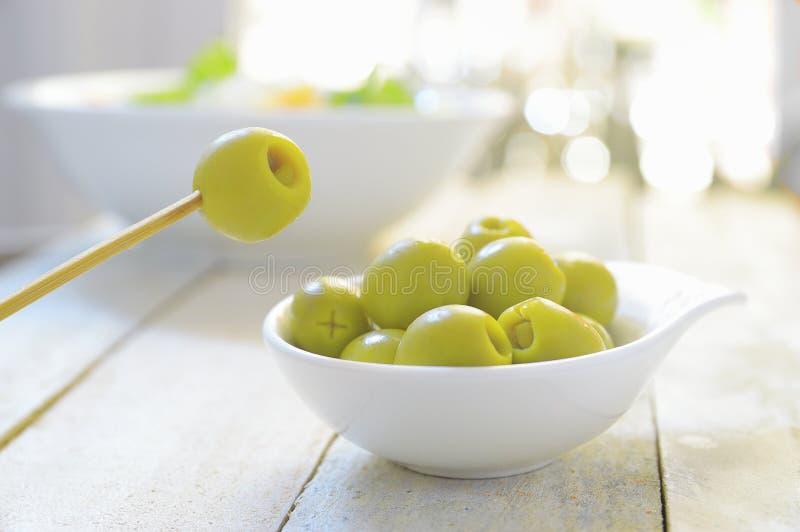 Типичные испанские тапы Некоторые заполненные оливки служили на плите на белом деревянном столе стоковое изображение