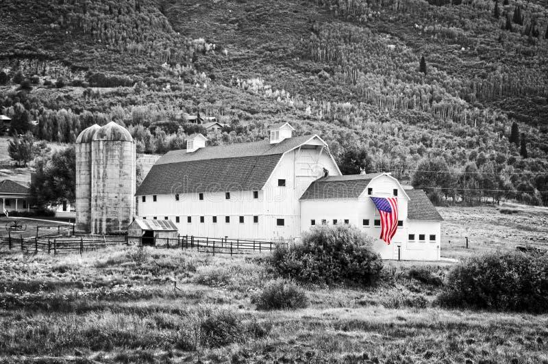Типичный винтажный американский амбар с американским флагом, Park City, Ютой - черно-белой фотографией, селективным цветом стоковые фотографии rf