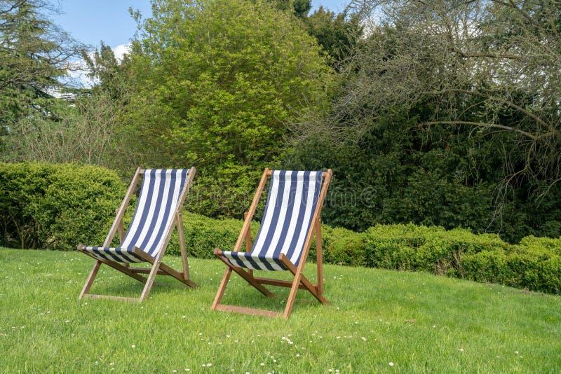 2 типичных английских deckchairs на лужайке в саде стоковое фото