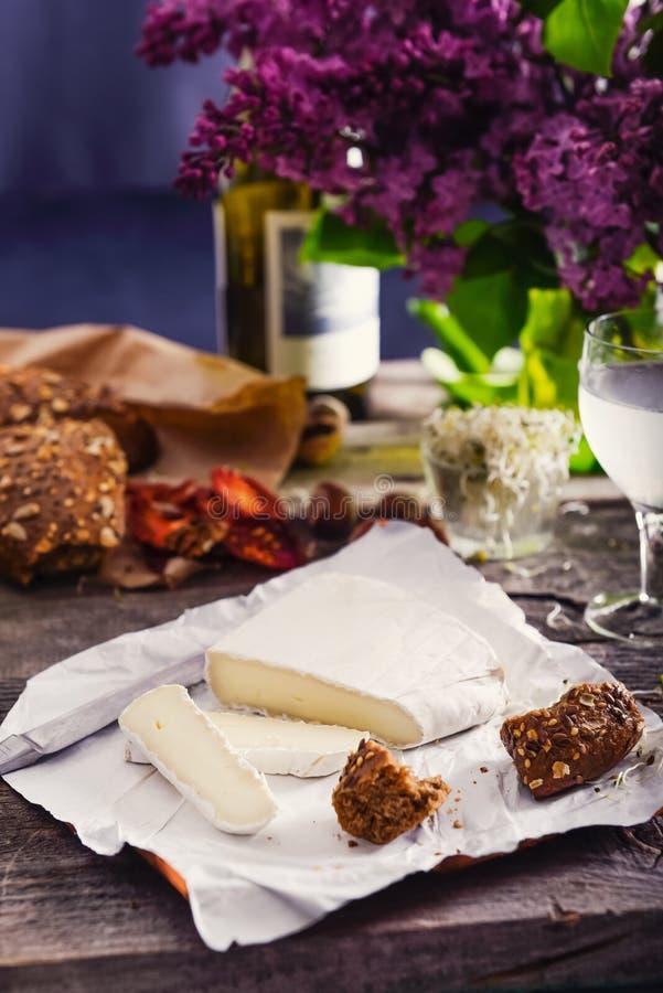 Тип бри сыра Сыр камамбера Свежий сыр бри и немногие куски с плюшкой вс-зерна, сухими томатами, бутылкой белого вина и стоковые изображения rf