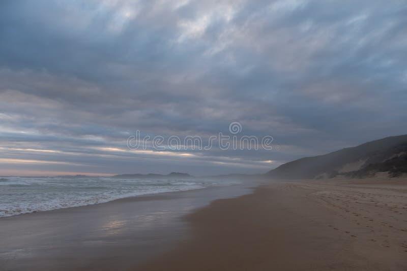 Тихий песчаный пляж на Brenton на море, Knysna, сфотографированном на заходе солнца, Южная Африка стоковое изображение