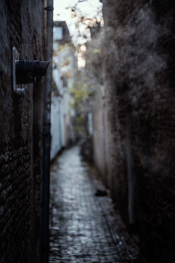 Тихий темный переулок с выхлопными трубами дуя сцена города дневного времени пара стоковая фотография