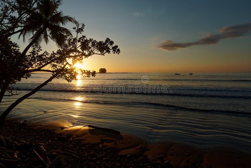 Тихоокеанское побережье Коста-Рика в Центральной Америке, выравнивая заход солнца с пальмами, океаном и облаками на красном небе стоковое изображение rf