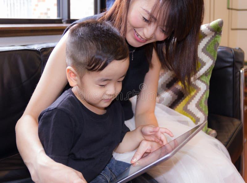 2-ти летний мальчик и мать, наблюдая содержание интернета с прибором таблетки стоковое фото