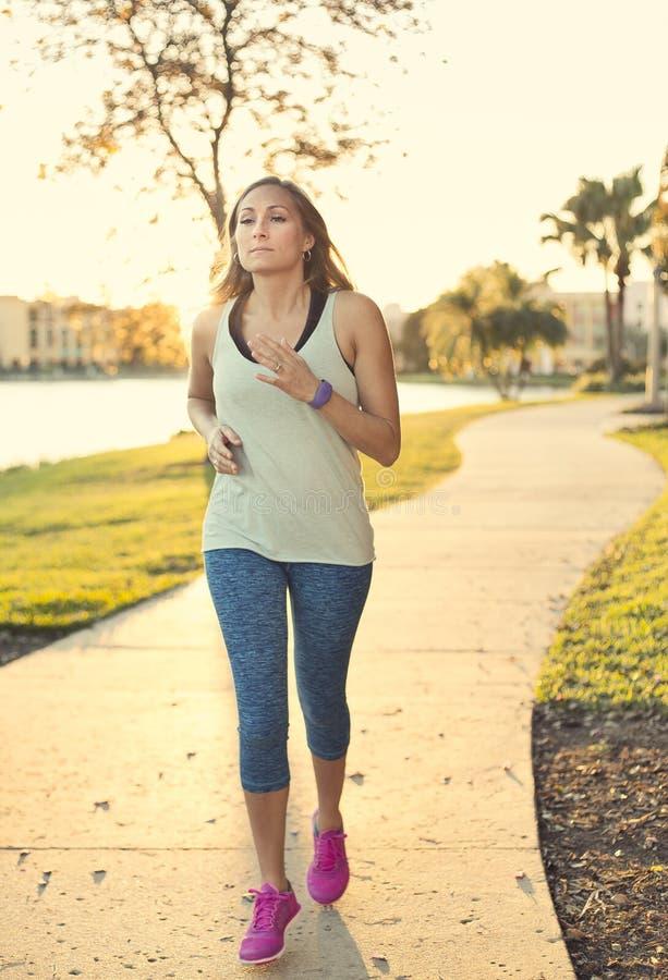 30-ти летняя здоровая женщина jogging в парке стоковая фотография