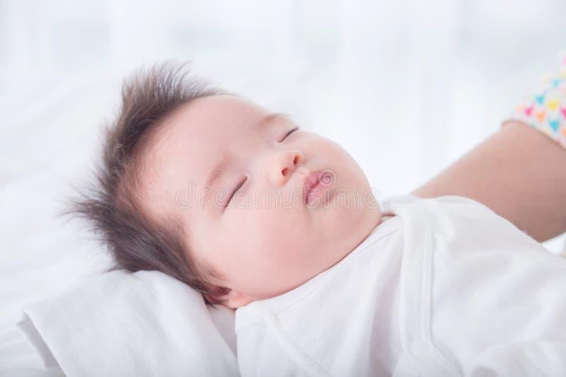 Ткань девушки нося белая спать на ее руке матери стоковые фото