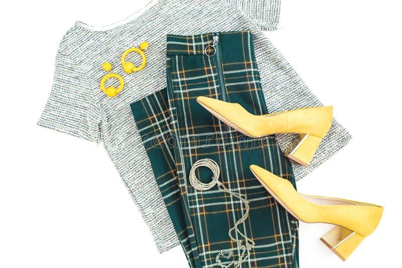 Ткань и аксессуары моды женщин Женская предпосылка с желтыми ботинками, серьгами, свитером и брюками checkered Плоское положение, стоковые изображения rf