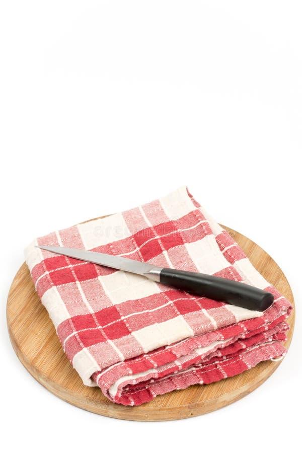 Ткань кухни красная белая с ножом и деревянной доской стоковое изображение rf