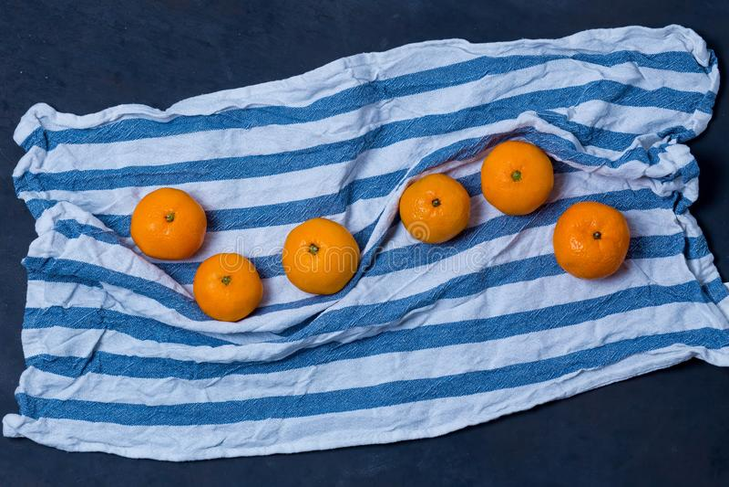 Ткань ткани полотенца кухни очень вкусного яркого сочного мандарина мандаринов голубая белая striped на синей черной предпосылке  стоковая фотография