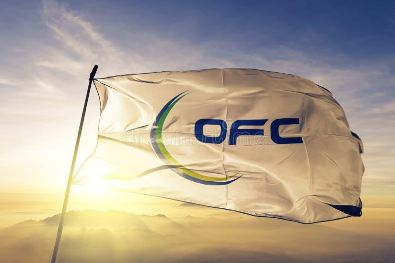 Ткань ткани ткани флага конфедерации футбола Океании развевая на верхнем тумане тумана восхода солнца бесплатная иллюстрация