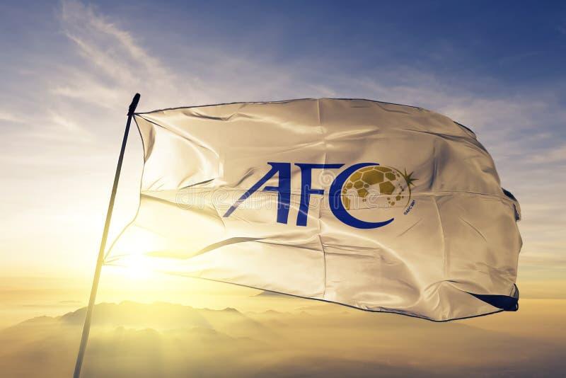 Ткань ткани ткани флага логотипа конфедерации азиатского футбола развевая на верхнем тумане тумана восхода солнца бесплатная иллюстрация