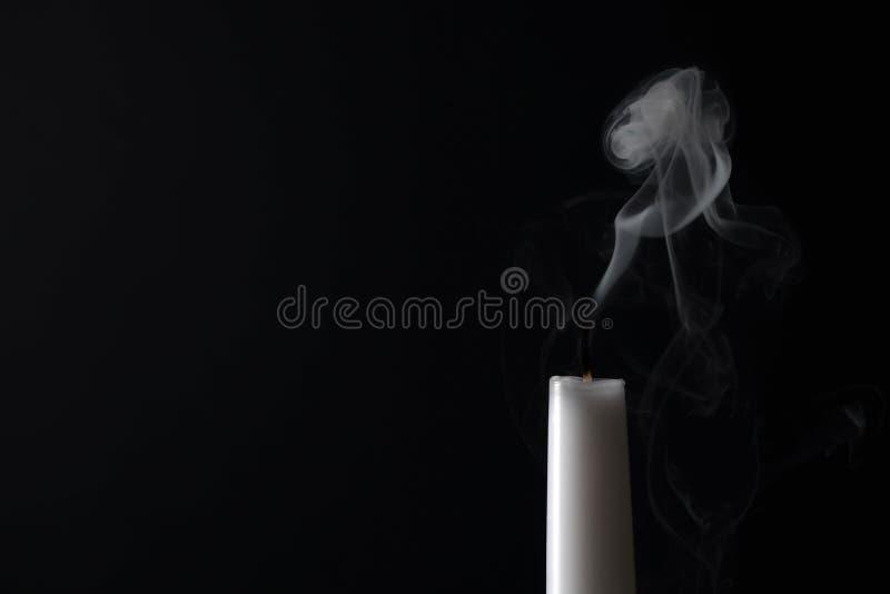 Тлея фитиль и дым свечи на темной предпосылке стоковые изображения