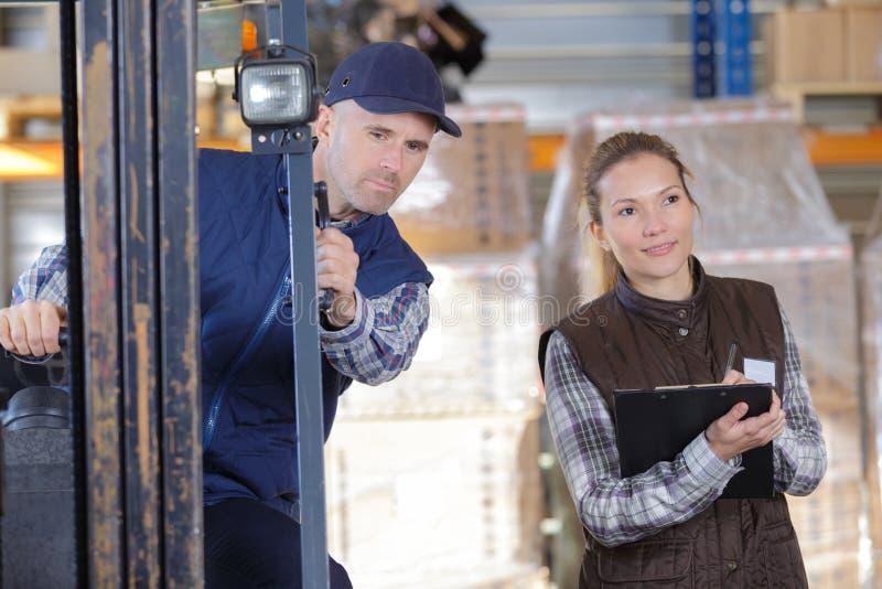 Товары работника и менеджера распределяя в складе стоковое фото