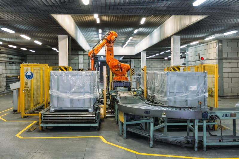 Товары фабрики по изготовлению упаковок робот-манипуляторов из конвейера в контейнер стоковая фотография rf