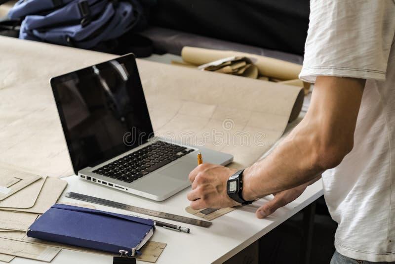 Товары широкого потребления дизайнерские на работе в мастерской Руки молодого мужчины стоковые изображения