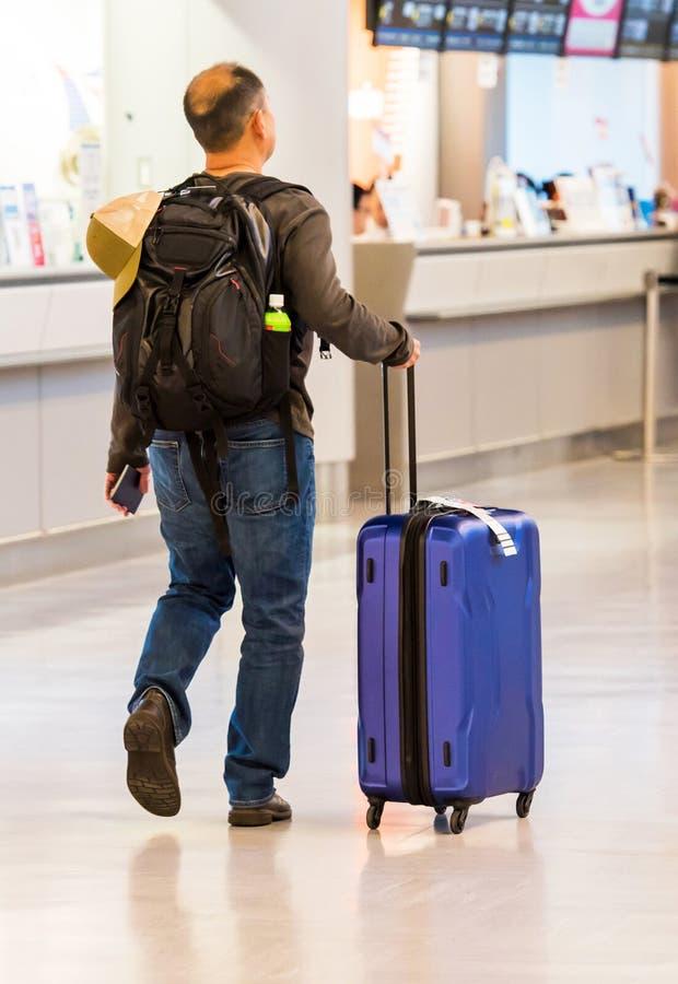 ТОКИО, ЯПОНИЯ - 7-ОЕ НОЯБРЯ 2017: Человек с голубым чемоданом в аэропорте задний взгляд С ½ иÐΜ  аР¿ Ð¸Ñ ÐžÐ выборочного фоку стоковое фото