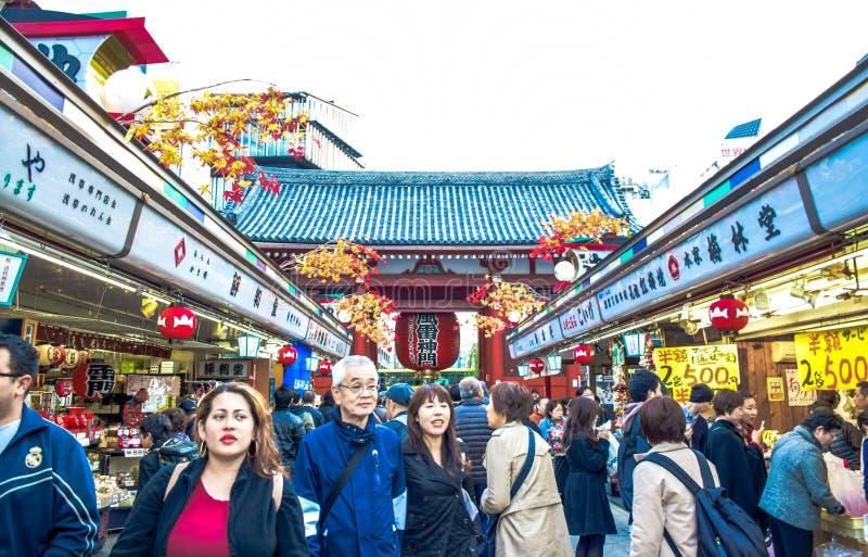 ТОКИО, ЯПОНИЯ: Туристы тратят их время в Nakamise-Dori, торговую улицу на обнаруженной местонахождение зоне виска Senso-ji стоковые фото