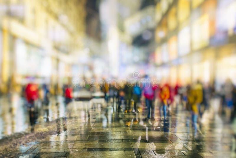 Толпа анонимных людей идя на занятую улицу города ночи стоковая фотография