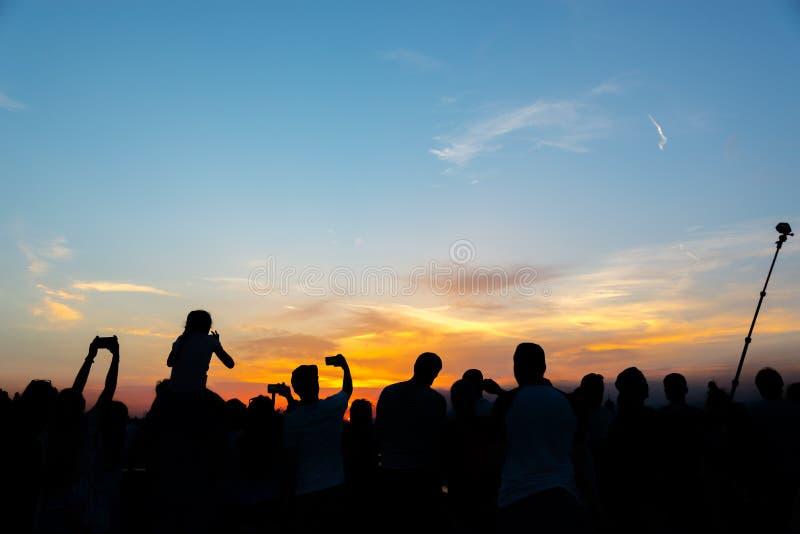 Толпа людей фотографируя заход солнца с мобильными телефонами и ручкой selfie на ноче лета в Флоренсе Италии стоковое фото