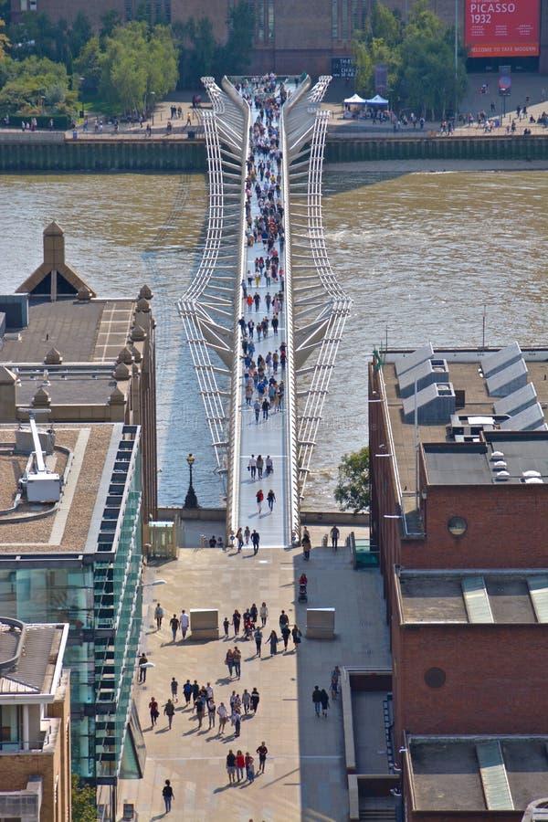 Толпа на мосте тысячелетия с Tate современным в предпосылке стоковые изображения rf