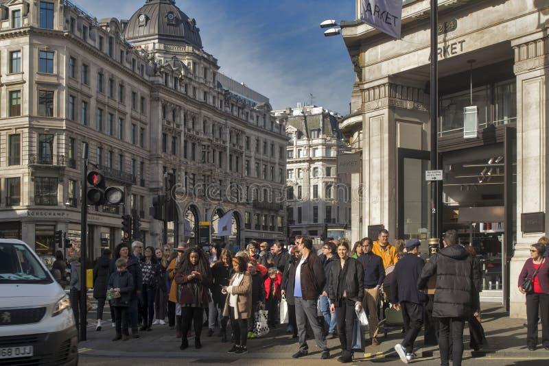 Толпа пересекает дорогу на пешеходный переход на правящей улице стоковое фото rf