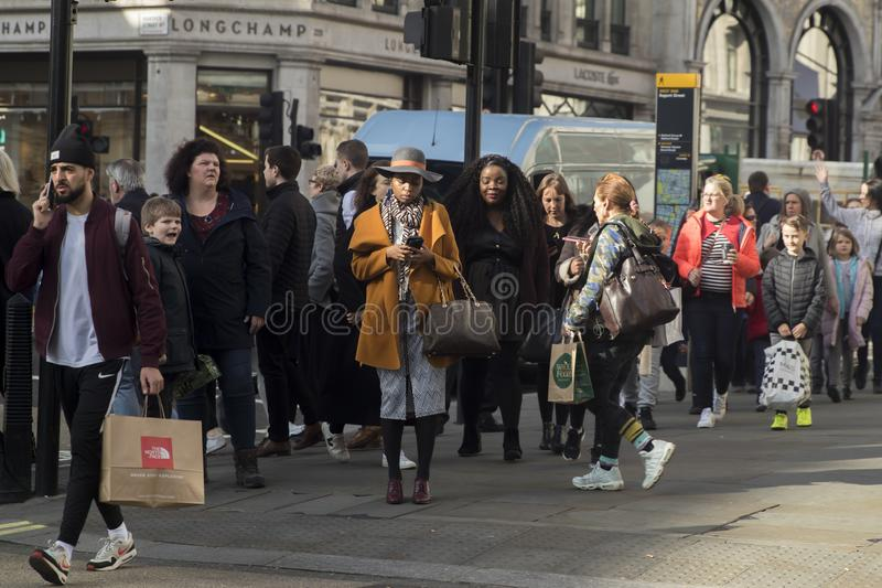 Толпа пересекает дорогу на пешеходный переход на правящей улице стоковые фотографии rf