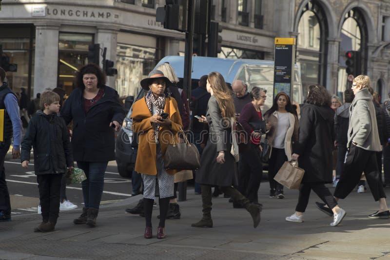 Толпа пересекает дорогу на пешеходный переход на правящей улице стоковые изображения rf