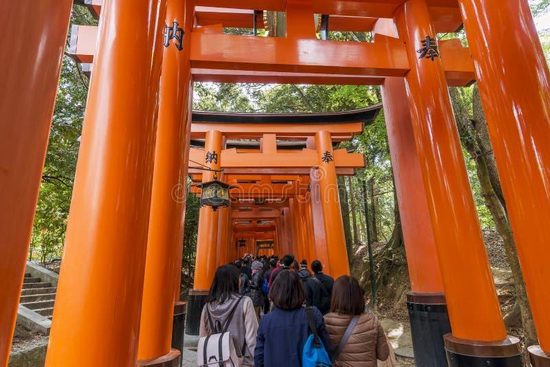 Толпа посетителей под стробами torii святыни Fushimi Inari в Киото, Японии стоковое изображение