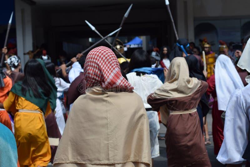 Толпа яростных женщин донимая gaher шарфа Иисуса Христа нося на площади веселя, посмешище, драма улицы, община празднует стоковые фото