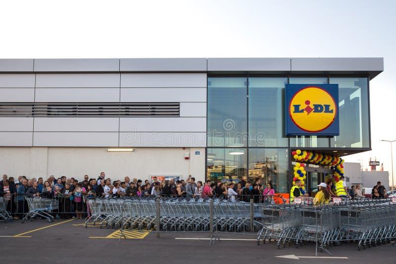 Толпитесь ждать в очереди для церемонии торжественного открытия 1-ого супермаркета Lidl в Сербии Lidl немецкая сеть супермаркетов стоковая фотография