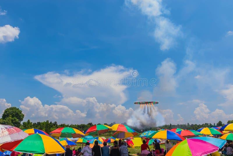 Толпитесь под красочным зонтика ждать ракету файрбола круга принимая к красивым небу и облаку Com стоковое изображение rf