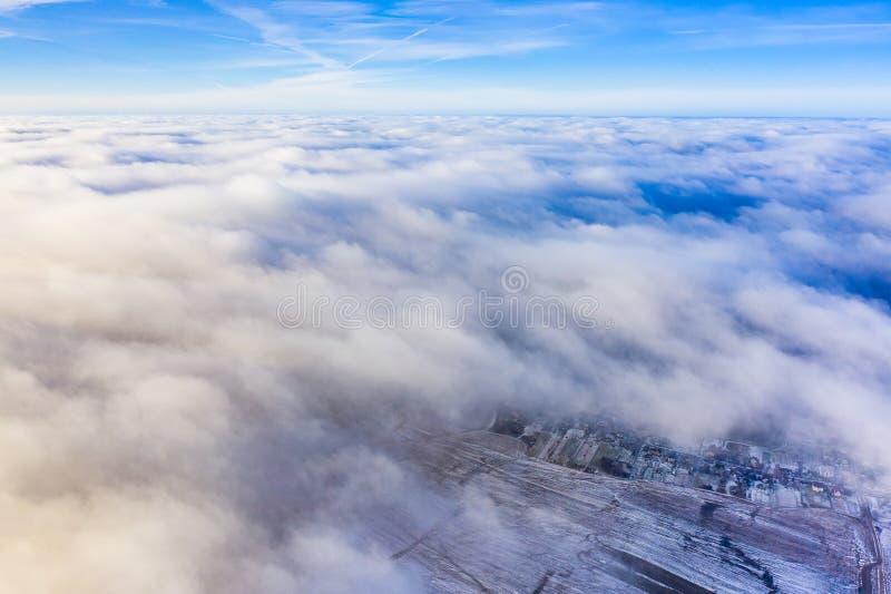 Толстое воздушное cloudscape Перемещать плоскостью Пригороды покрытые со снегом стоковое фото rf