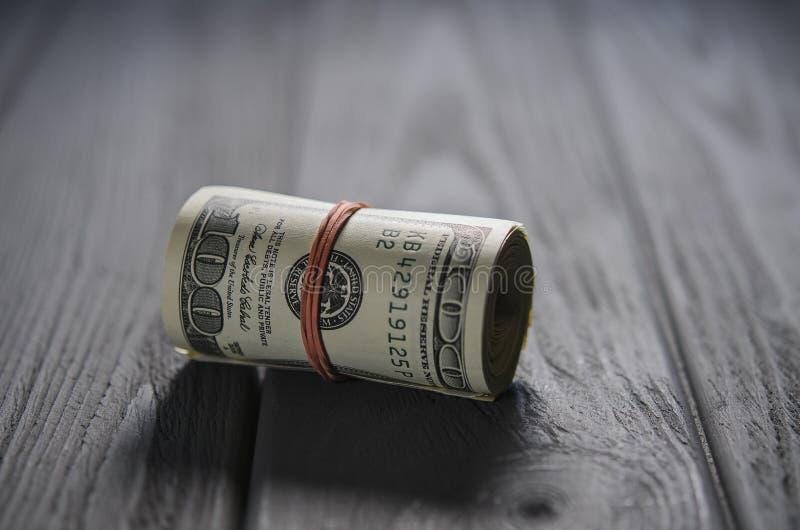 Толстый крен 100 банкнот доллара связал красную круглую резинку лежит на серой деревянной таблице стоковые фото