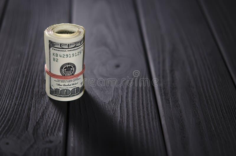 Толстый крен 100 банкнот доллара связал красную круглую резинку лежит на черной деревянной таблице стоковая фотография